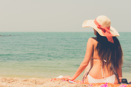 Beautiful asian bikini woman sitting on beach  looking at  the sea with white large hat vintage retro filter effect for exotic holiday romance relaxing vacation concept
