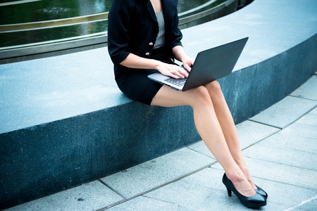 Young business leader agile working concept. Young business woman working outside office in outdoor on sunny day with laptop. Attractive woman with black jacket, skirt, shoes with notebook outdoor. Stock Photo