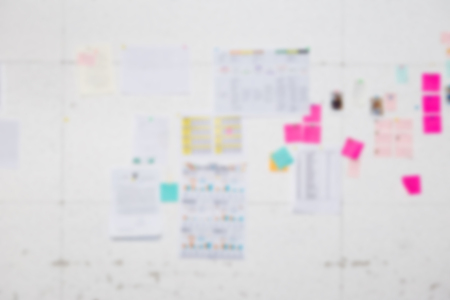 Blur background of white board with many business papers and reports stick on the white wall. With business report such as sale performance report, line chart, bar chart. For brain storming concept.