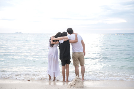 Young family on beach holding each other. Young happy interracial family on beach hugging together. Asian woman, Caucasian man, young boy. Young mixed race family concept.