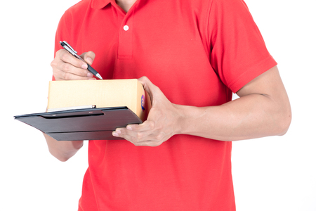 Young logistic career concept. Happy delivery man with box and taking notes. Isolated on white background. Asian chinese fit man in red polo shirt and jeans with red hat in his early twenties.