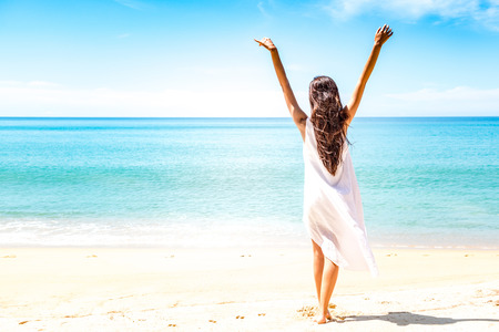 Beautiful young single white woman on beach. Standing happy freedom pose relaxing, wearing white dress.