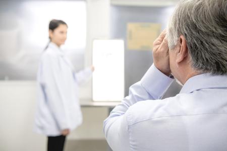 Augenoptiker mit Patient. Junger chinesischer Arztoptiker mit ihrem älteren chinesischen Mannpatienten im Optikerzimmer untersucht sein Auge. Echtes Optikerzimmer im Krankenhaus. Medizinisches Konzept.