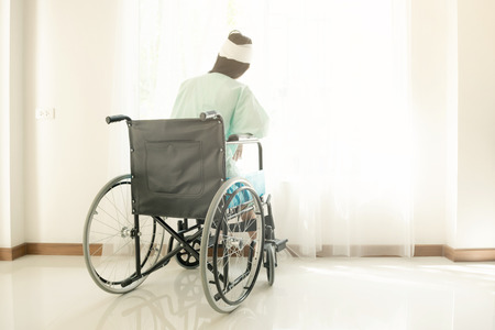 Young woman in hospital wheel chair. Looking at window. Beautiful chinese woman. Medical, health insurance concept.