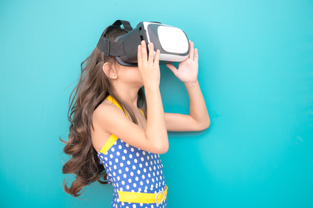 Young VR girl isolated white. Pretty early teenage girl portrait with VR headset. Exciting pose. Future technology and education concept.