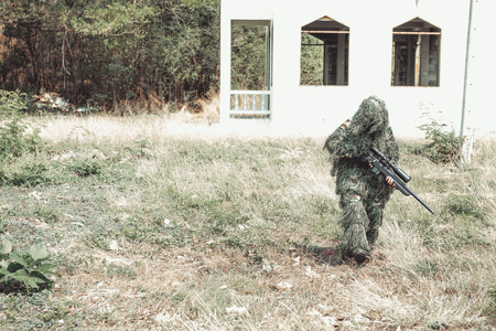 Sniper in urban combat training. Full ghillie camo suit and a high power sniper rifle. In urban combat training ground. Walking to the location.