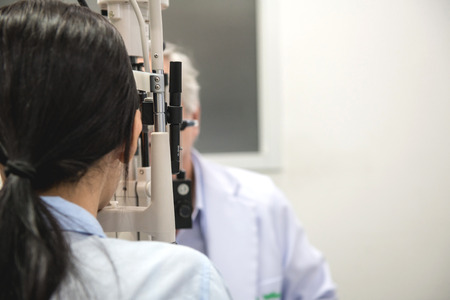 Opitcian with patient. Senior chinese optician with his asian woman patient in Optician room examine her eye. Real optician room in hospital. Medical concept.