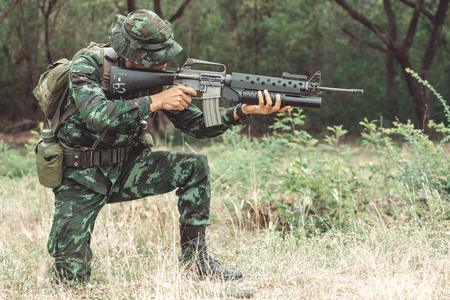 Soldier reloading his assault rifle. Chinese professional soldier reloading his weapon and putting his magzine inside his gun. Kneeing down action. Stock fotó