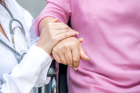 Nurse with senior patient in park holding hand. Senior disable woman in wheelchair relaxing and being comfort by a chinese female nurse. Stock fotó