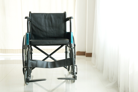 Empty wheel chair in hospital. With window and sun light on the right.