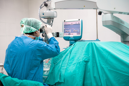 Eye surgeon at work. Young caucacian male surgeon with his beautiful chinese assistant woman performing surgery on a senior patient. Real operating theater room. Medical concept. Stock fotó