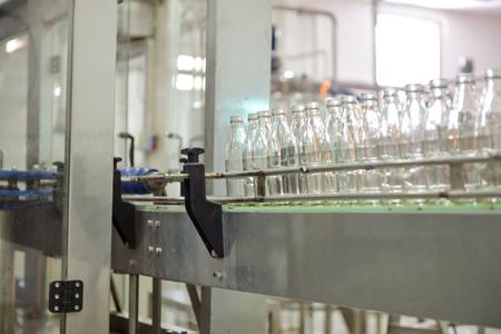 Beverage production line background. A conveyor belt full of empty glass bottle going into bottle filling machine. Beverage manufacturing concept.