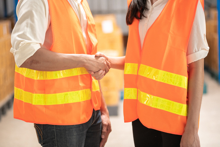 Warehouse operator teamwork. Male and female warehouse operators shaking hand. Warehouse in background.