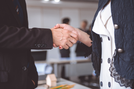 Businessman shake hand together. Young asian businesswoman in dress with man shaking hand with his employee.
