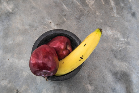 impotence: large banana and apples on strong concrete