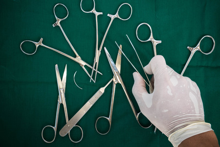 techie: Hand holding forceps, with instruments for surgery