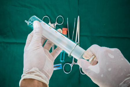 techie: Hands holding big glass syringe, with instruments for surgery background Stock Photo