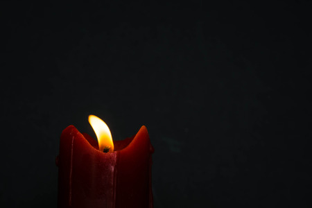 glimmer: old red candle with glimmer light flame on nice grey background, with blank upper space