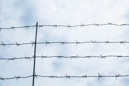 fence: Shallow depth of field, old barbed steel wire against blue sky Stock Photo
