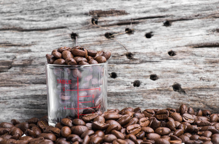 shot glass: Roasted coffee beans in coffee shot glass and around with wood background Stock Photo
