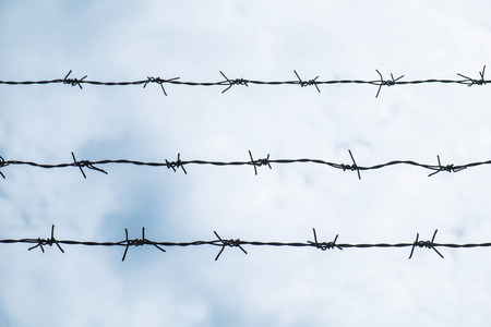 dangerous ideas: Shallow depth of field, old barbed steel wire against blue sky Stock Photo
