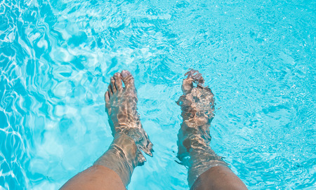 Male feet dipping in swimming pool