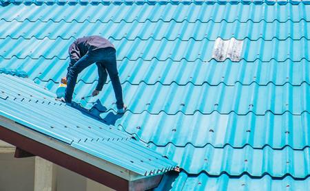 Contractor repairing broken roof