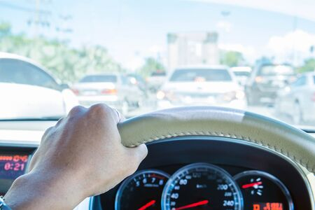 wheel: Hand of driver holding steering wheel, with traffic view in the city Stock Photo