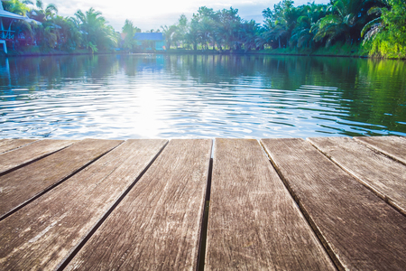 Footbridge: antique wooden pier on the lake with sunlight effects Stock Photo