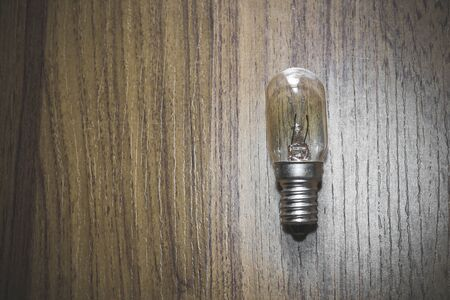 metal filament: Vintage light bulb on wooden background Stock Photo