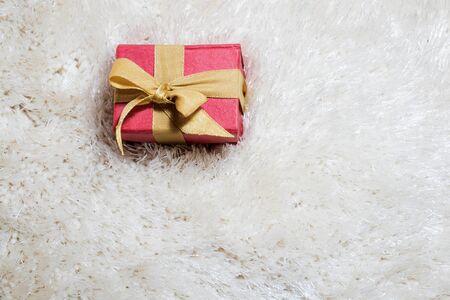 red carpet background: red gift box on white carpet, vintage tone