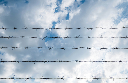 oppress: Silhouette barbed wire against blue sky Stock Photo