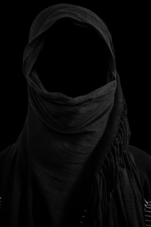 Faceless man under black veils, isolated on black background