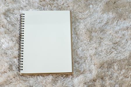 white carpet: Notebook on white carpet