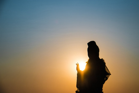 mercy: Silhouette, Goddess of Mercy Guan Yin, against the sun in sunset