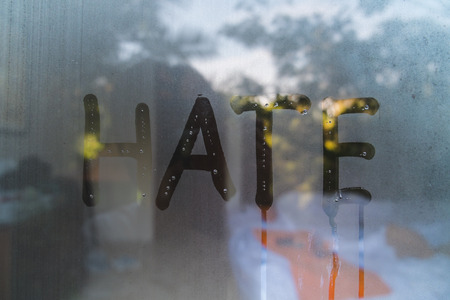 trickling: the word HATE, draw on hazy glass in the morning