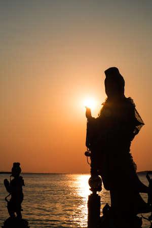 goddess of mercy: Silhouette, Goddess of Mercy Guan Yin, against the sun in sunset