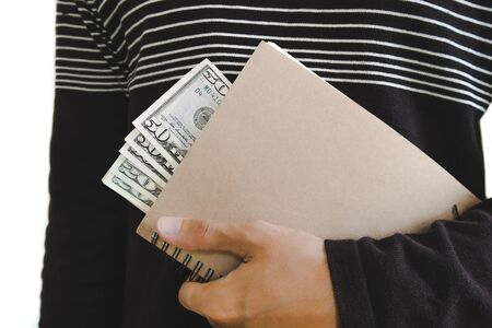 venality: A man holding book with cash hiding inside, isolated on white background