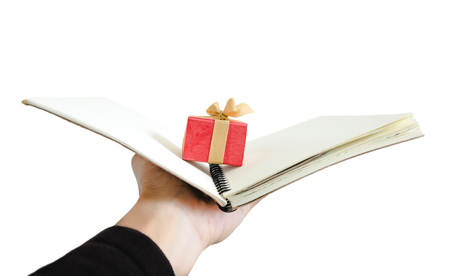 analogy: Hand holding opened notebook with little gift box inside, isolated on white background Stock Photo