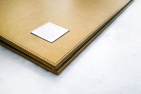 yellow design element: Abstract gold leather menu covered, on white marble stone table