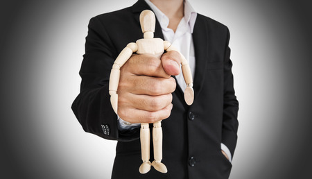 impotent: Businessman holding wooden figure, abstract concept