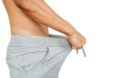 Aziatische kerel trekken warme broek, geïsoleerd op een witte achtergrond Stockfoto