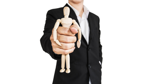 puppet master: Businessman holding wooden figure, abstract concept, isolated on white background Stock Photo