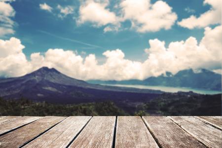 de focus: Wooden terrace with blurred de focus landscape of mountain and sky background, vintage tone