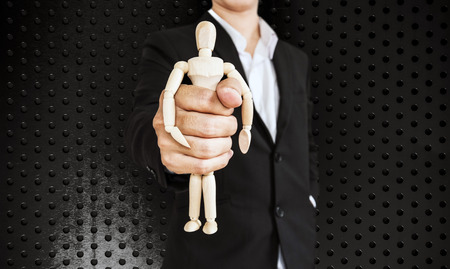 impotent: Businessman holding wooden figure, on black aluminum texture background