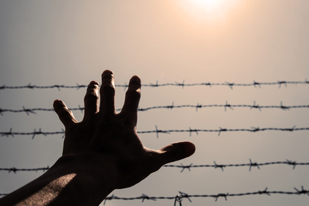 emanation: Silhouette hand extending to the sky with barbwire and sunlight , vintage tone