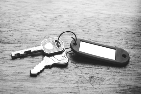 fob: Keys with blank key fob on wooden background, vintage tone, black and white
