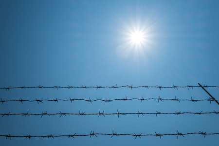 oppress: Barbwire against sun flare effects on blue sky