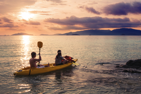 Couple kayaking in sunset, holiday vacation summer times, dating, romantic, vintage tone