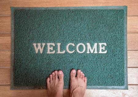 welcome mat: green foot scraper mat on wooden floor with barefoot standing
